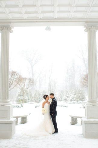 newlyweds under snowy columned terrace