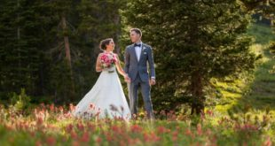 newlyweds walk among wildflowers on Colorado mountain.jpg