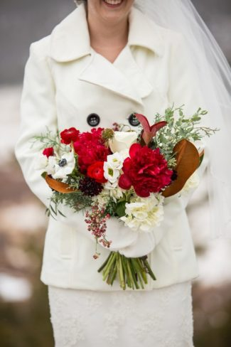 white suite bride with red bouquet