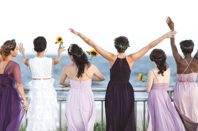bachelorette party holding sunflowers looking at beach