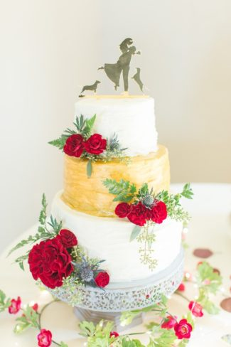 blue thistles and red carnation on wedding cake