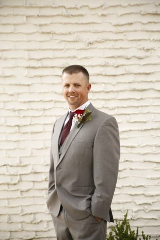 groom against white brick wall