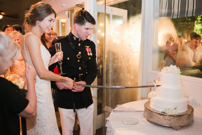 newlyweds cut cake with sword