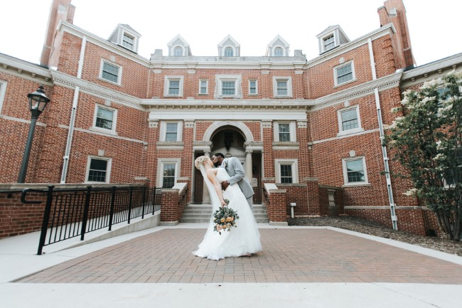 bride and groom in front of university building