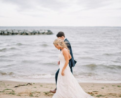 newlyweds walk on beach in Maryland