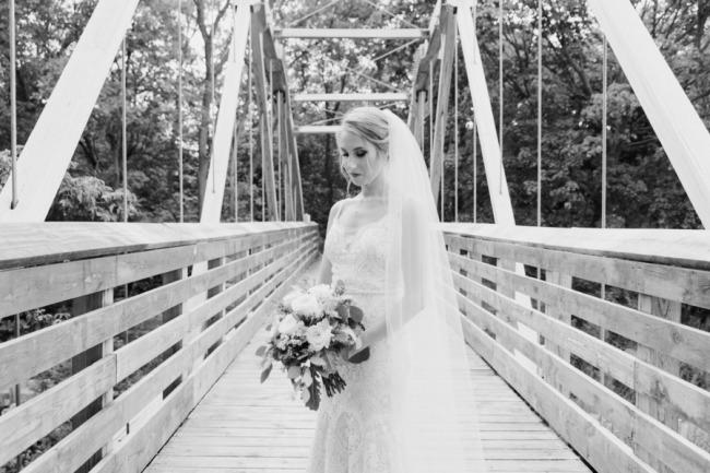 black and white of bride on bridge