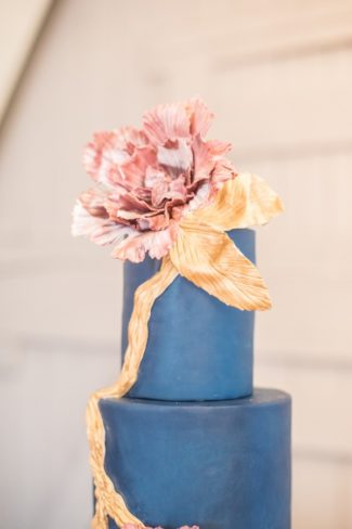 blue tiered cake with gold ribbon