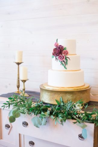 cake with greenery set against white wall