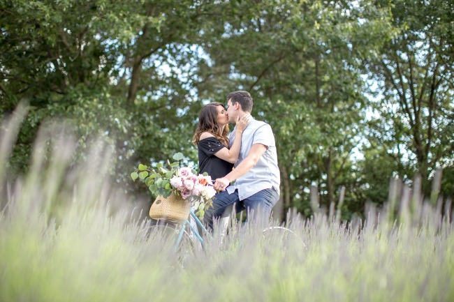 foreground grass blur of couple kissing on bicycle