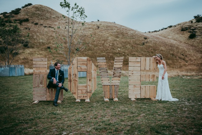 newlyweds play on giant LOVE wood sign