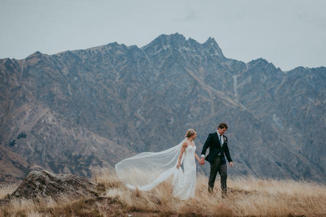 newlyweds walk in hills
