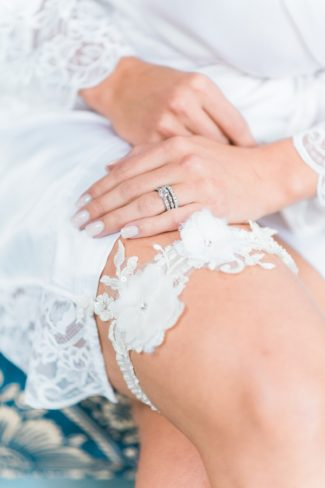 styled bride showing white garter belt