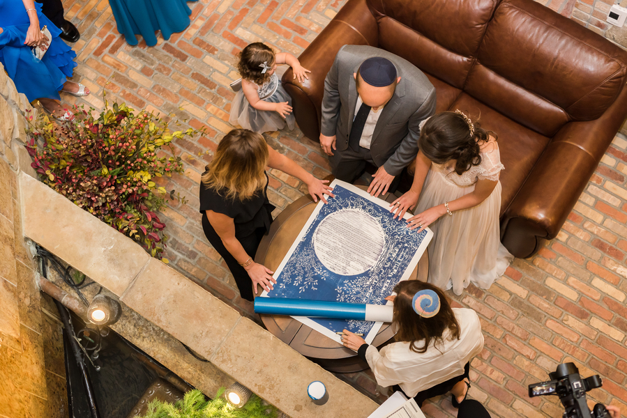 overhead shot of couple and witness touching Ketubah