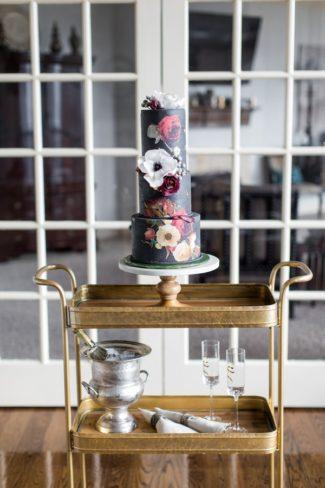 black wedding cake on gold serving trolley