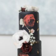 black wedding cake with white and red flowers