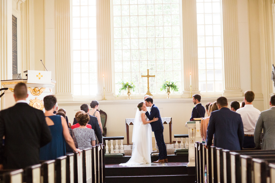 bride and groom kissing during church wedding ceremony