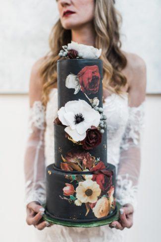 bride holding black wedding cake