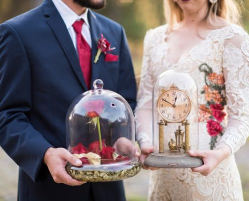 couple holding styled beauty and beast decor