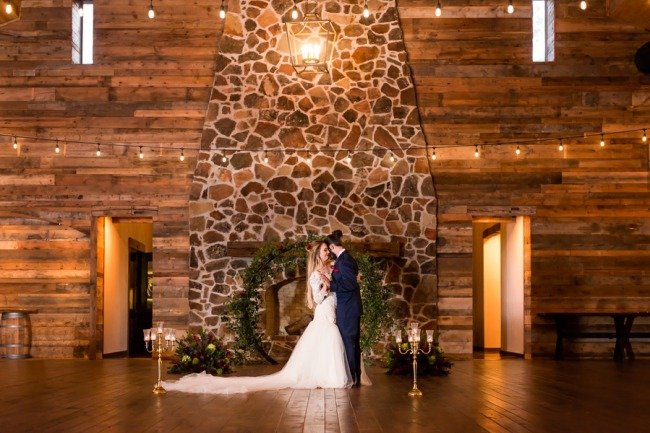 couple in front of fireplace at vineyard