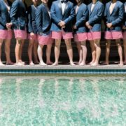 groomsmen lined up in red striped trunks with blazers