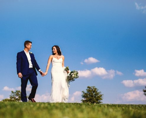 newlyweds with blue sky backdrop
