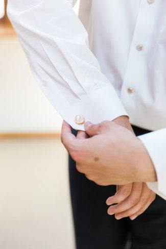 putting on cufflinks