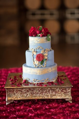 red rose topped cake on silver square stand