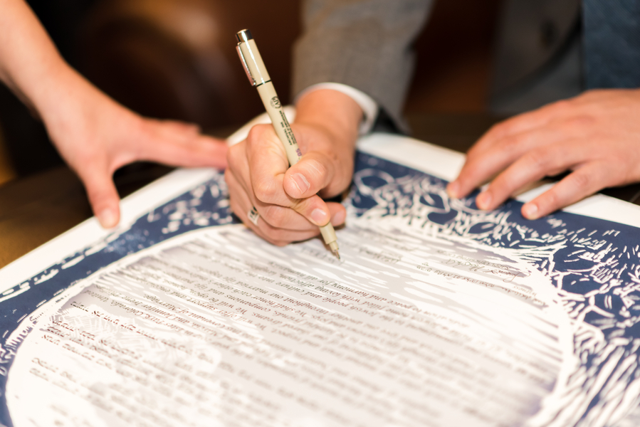 couple sign a ketubah at a real wedding