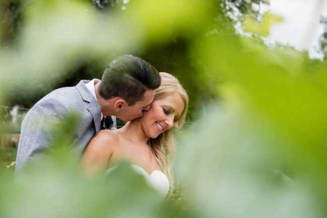 peaking through vines at newlyweds
