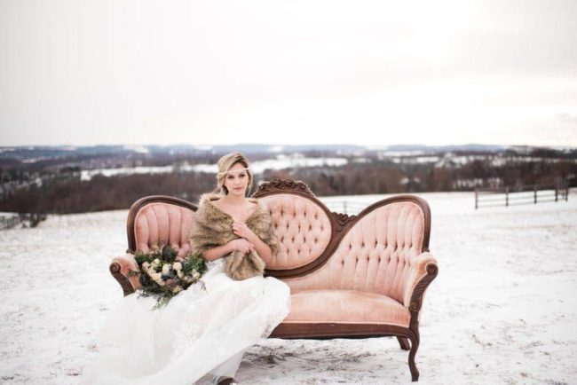 styled-fur-bride-on-vintage-couch-outdoors-in-field