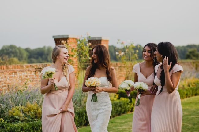 bridesmaids-and-bride-walk-in-garden