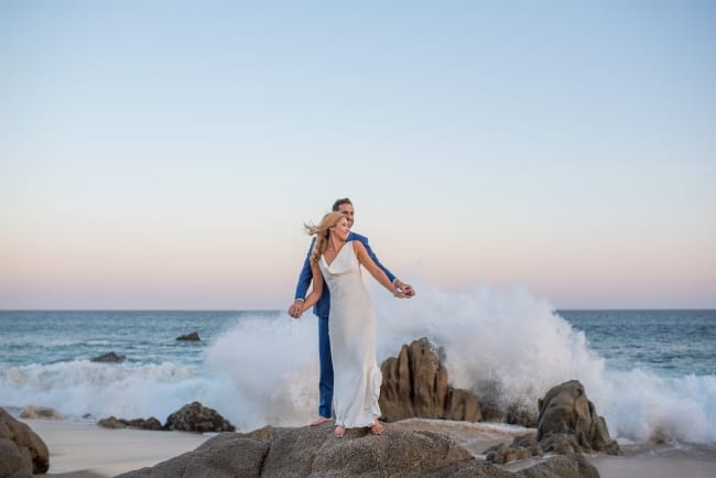 Los Cabos newlyweds on spalshing rocks