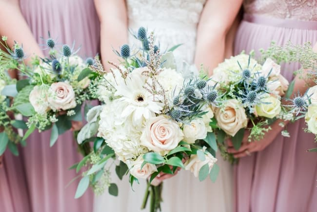 bouquets with blue thistle and cream roses