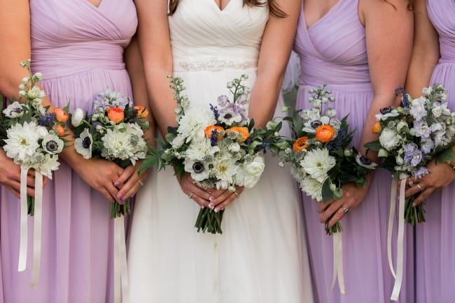 bridesmaids in lilac dresses with bouquets