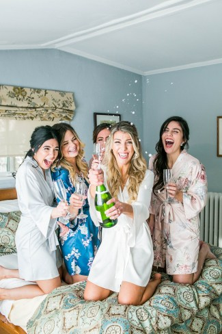 Bride with bridesmaids wearing silk BHLDN robes gettig ready morning of