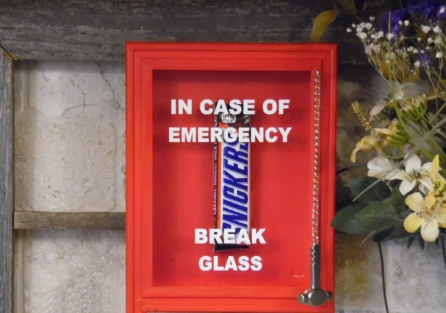 snickers chocolate bar under emergency glass