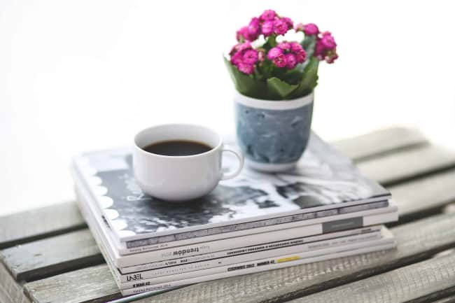 stack of magazines with coffee mug and flowers on top