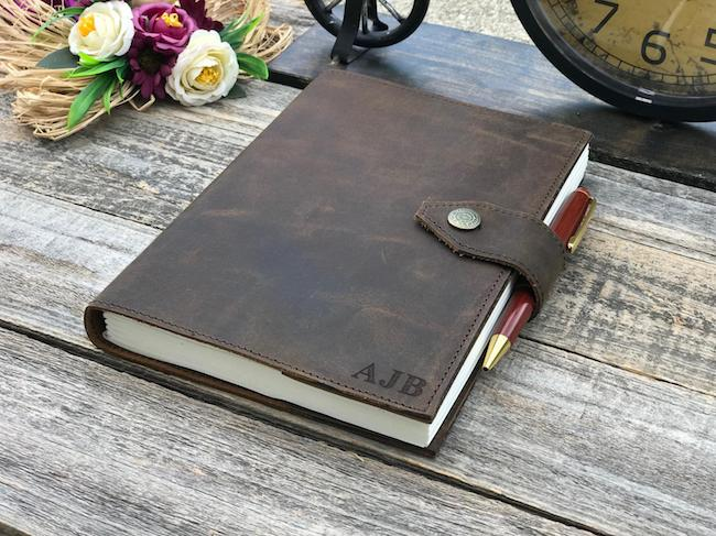 brown leather-bound journal with clasp and pen