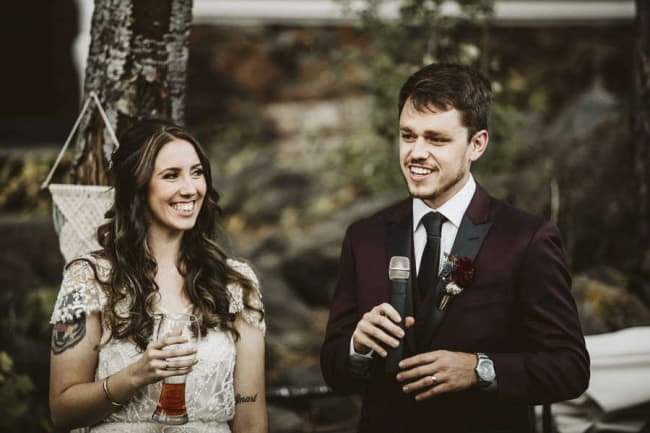 groom giving speech with bride standing next to him