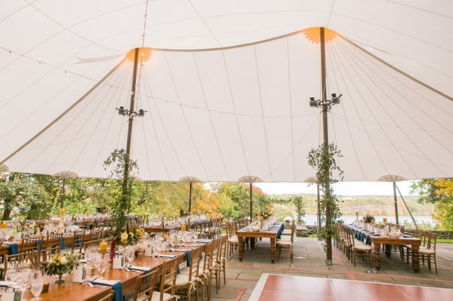 large wedding tent with tables beneath