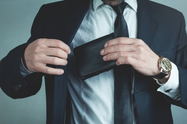 man putting wallet in his jacket pocket