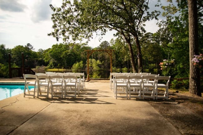 white chairs and wooden arch wedding setup