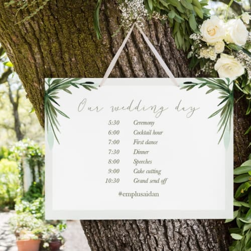 wedding schedule sign hanging in tree