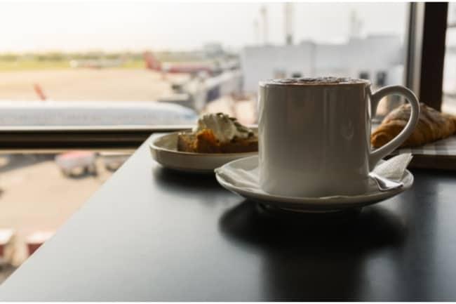 Café caliente con desayuno en el salón del aeropuerto